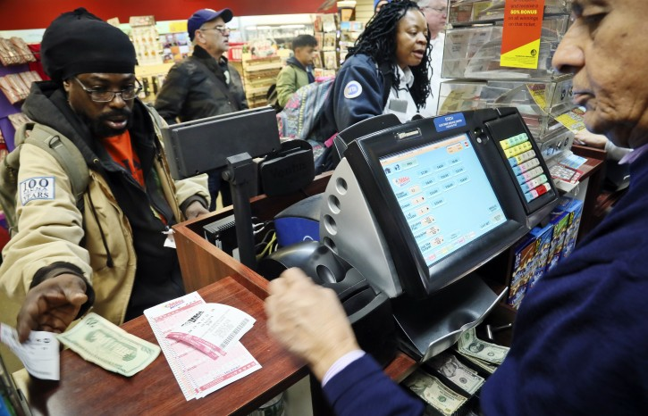 FILE - Lottery players buy tickets Friday Oct. 19, 2018, in New York.  (AP Photo/Bebeto Matthews)