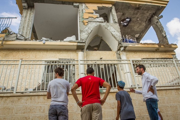 People gather outside the scene where a building was hit by a rocket fired from the Gaza Strip in the southern Israeli city of Beersheba, on October 17, 2018. Photo by Flash90