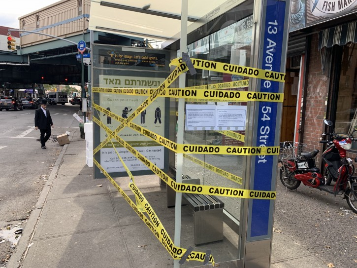 An advertisement on a bus shelter reading 'Venishmartem Me'od Lenafshoseichem' (to be careful with our lives) is seen taped off in Borough Park on Oct 16, 2018. About 1,400 bus shelters across NYC have been shut down for safety inspections after one collapsed earlier this month in Staten Island.