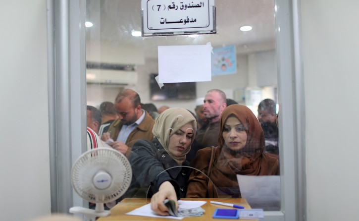 Palestinian Hamas-hired employees receive full salaries for the first time in years, in the southern Gaza Strip November 9, 2018. REUTERS/Ibraheem Abu Mustafa