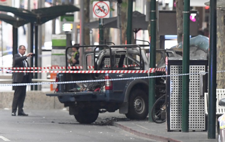 A burnt out vehicle is seen on Bourke Street in Melbourne, Friday, Nov. 9, 2018. A knife-wielding man stabbed two people, one fatally, in Australia's second-largest city on Friday in an attack likely linked to terrorism, police said. The attack during the afternoon rush hour brought central Melbourne to a standstill.(James Ross/AAP Image via AP)