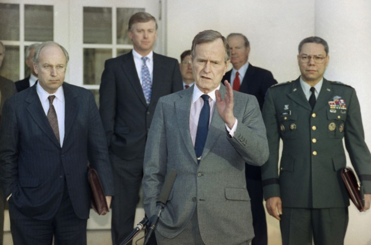 FILE - In this Feb. 11, 1991, file photo, President George H.W. Bush talks to reporters in the Rose Garden of the White House after meeting with top military advisors to discuss the Persian Gulf War. From left are, Defense Secretary Dick Cheney, Vice President Dan Quayle, White House Chief of Staff John Sununu, the president, Secretary of State James A. Baker III, and Joint Chiefs Chairman Gen. Colin Powell. Bush died at the age of 94 on Friday, Nov. 30, 2018, about eight months after the death of his wife, Barbara Bush. (AP Photo/Ron Edmonds, File)