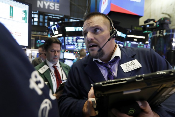 FILE- In this Dec. 3, 2018, file photo trader Michael Milano, right, works on the floor of the New York Stock Exchange. AP