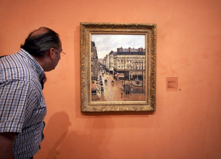 """FILE - This May 12, 2005, file photo shows an unidentified visitor viewing the Impressionist painting called """"Rue St.-Honore, Apres-Midi, Effet de Pluie"""" painted in 1897 by Camille Pissarro, on display in the Thyssen-Bornemisza Museum in Madrid. AP"""