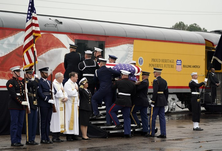 The flag-draped casket of former President George H.W. Bush is carried by a joint services military honor guard Thursday, Dec. 6, 2018, in Spring, Texas, as it is placed on a Union Pacific train. (AP Photo/David J. Phillip, Pool)