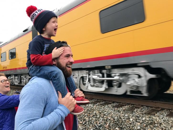 Ryder Davis, 3, watches the memorial train for President George H.W. Bush pass through Pinehurst, Texas, atop the shoulders of his father, 27-year-old Matthew Davis, on Thursday, in Pinehurst, Texas. (AP Photo/Nomaan Merchant)