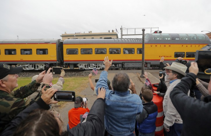 People pay their respects as the train carrying the casket of former President George H.W. Bush passes through Novasota, Texas Thursday, Dec. 6, 2018. (AP Photo/Gerald Herbert)