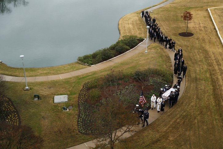 The flag-draped casket of former President George H.W. Bush is carried by a joint services military honor guard followed by family members for burial at the George H.W. Bush Presidential Library and Museum Thursday, Dec. 6, 2018, in College Station, Texas. (AP Photo/Jeff Roberson, Pool)