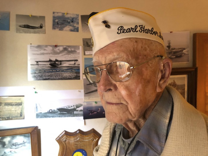 Retired U.S. Navy Cmdr. Don Long stands next to a wall of photographs on Friday, Dec. 7, 2018 at his home in Napa, Calif. Long was alone on an anchored military seaplane in the middle of Kaneohe Bay, across the island from Pearl Harbor, when Japanese warplanes attacked Hawaii on Dec. 7, 1941, watching from afar as the bombs and bullets killed and wounded thousands. When the gunfire finally reached his plane, setting the aircraft ablaze, he jumped into the water and found himself swimming through fire to safety. (AP Photo/Eric Risberg)