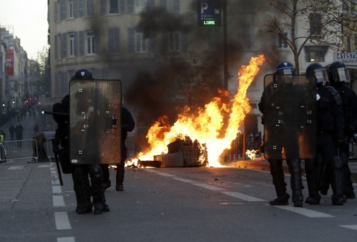Riot police officer stand in front a burning trash bin during clashes, Saturday, Dec. 8, 2018 in Marseille, southern France. French riot police fired tear gas and water cannon in Paris on Saturday, trying to stop thousands of yellow-vested protesters from converging on the presidential palace to express their anger at high taxes and French President Emmanuel Macron. (AP Photo/Claude Paris)