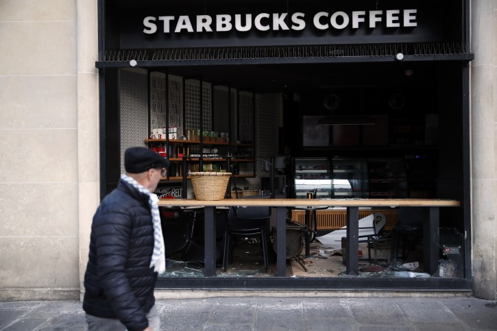 A man walks near a coffee shop whose windows are broken in Paris, Sunday, Dec. 9, 2018.Paris monuments reopened, cleanup workers cleared debris and shop owners tried to put the city on its feet again Sunday, after running battles between yellow-vested protesters and riot police left 71 injured and caused widespread damage to the French capital. (AP Photo/Christophe Ena)