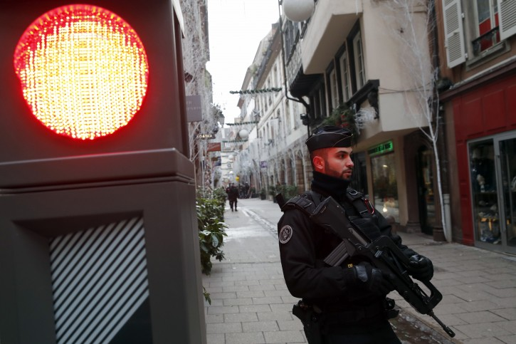 French police officer stands guards following a shooting in the city of Strasbourg, eastern France, Wednesday, Dec. 12, 2018. A man who had been flagged as a possible extremist sprayed gunfire near the city of Strasbourg's famous Christmas market Tuesday, killing three people, wounding 12 and sparking a massive manhunt. France immediately raised its terror alert level. (AP Photo/Christophe Ena)