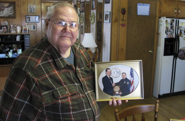 In this Jan. 17, 2019 photo, former Richford police chief Richard Jewett holds a photo of himself in Highgate, Vt., shaking hands with former FBI Director William Sessions. Jewett was being honored for the night in 1987 when he apprehended a man who carried a bomb into the United States from Canada.  (AP Photo/Wilson Ring)
