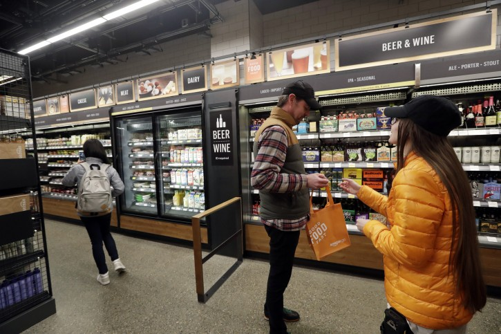 FILE- In this Jan. 22, 2018, file photo, a worker, right, looks at the ID of a shopper at the wine and beer area inside an Amazon Go store in Seattle. Get ready to say good riddance to the checkout line. A year after Amazon opened its first cashier-less store, startups and retailers are racing to get similar technology in other stores throughout the world, letting shoppers buy groceries without waiting in line. (AP Photo/Elaine Thompson, File)