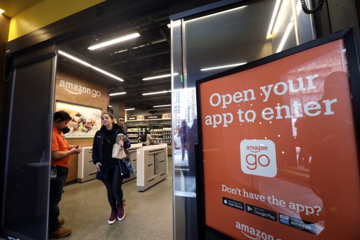 FILE- In this Jan. 22, 2018, file photo, a shopper departs an Amazon Go store in Seattle. Get ready to say good riddance to the checkout line. A year after Amazon opened its first cashier-less store, startups and retailers are racing to get similar technology in other stores throughout the world, letting shoppers buy groceries without waiting in line. (AP Photo/Elaine Thompson, File)
