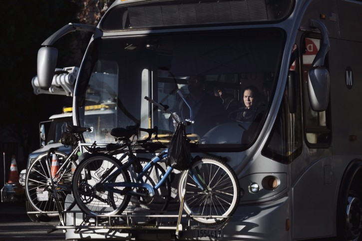 FILE- In this Jan. 9, 2019, file photo a Los Angeles Metro bus driver makes her way through an intersection in Los Angeles. The new tax law eliminated the deduction owners could take for subsidizing their employees' commuting costs. Similar to their decisions about entertainment expenses, owners must decide whether they want to continue giving employees money toward their mass transit fares or parking tabs. (AP Photo/Richard Vogel, File)