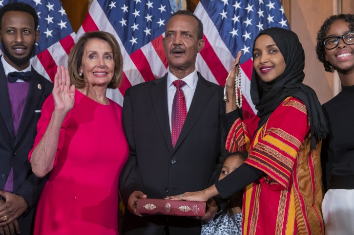 FILE - Democratic Representative from Minnesota Ilhan Omar (2-R), uses the Koran of her late grandfather while posing with new Democratic Speaker of the House Nancy Pelosi (2-L), during the first day of the 116th Congress at the US Capitol in Washington, DC, USA, 03 January 2019.  EPA-EFE/ERIK S. LESSER