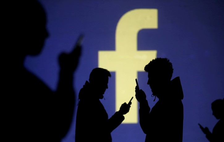 Silhouettes of mobile users are seen next to a screen projection of Facebook logo in this picture illustration taken March 28, 2018. REUTERS/Dado Ruvic
