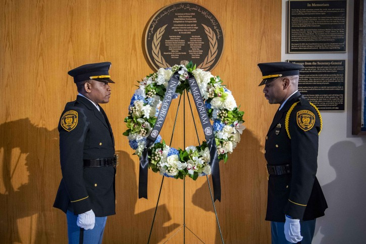 Two United Nations security officers stand beside a memorial wreath during a ceremony at United Nations headquarters, Friday March 15, 2019, for U.N. personnel that were aboard Ethiopian Airlines Flight ET302. At least 21 U.N. personnel were among the 157 people from 35 countries who died Sunday morning when an Ethiopian Airlines Boeing 737 MAX 8 jetliner crashed shortly after takeoff from Addis Ababa en route to Nairobi, Kenya. (United Nations Photo by Manuel Elias via AP)