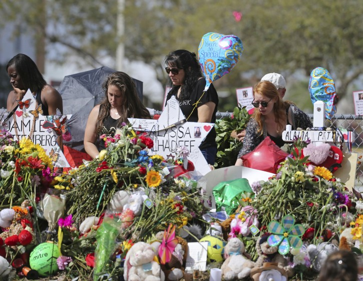 FILE - In this Feb. 25, 2018 file photo, mourners bring flowers as they pay tribute at a memorial for the victims of the shooting at Marjory Stoneman Douglas High School, in Parkland, Fla. The community of Parkland, Florida, is focusing on suicide prevention programs after two survivors of the Florida high school massacre there killed themselves this month.  (David Santiago/Miami Herald via AP, File)