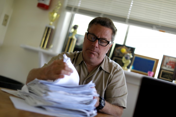 Scott Rosmarin, owner and operator of Rosmarins Day Camp and Cottages, sorts campers' immunization forms at the camp office in Monroe, New York, U.S., May 20, 2019. Picture taken May 20, 2019. REUTERS/Mike Segar