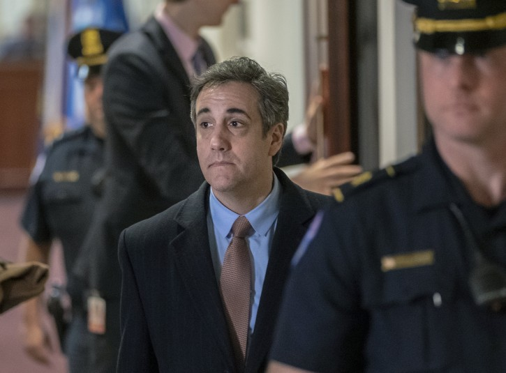 """Michael Cohen, President Donald Trump's former lawyer, tells reporters as he departs that he will """"continue to cooperate"""" with the House Intelligence Committee as he prepares for a three-year prison sentence for lying to Congress and other charges, at the Capitol in Washington, Wednesday, March 6, 2019. (AP Photo/J. Scott Applewhite)"""