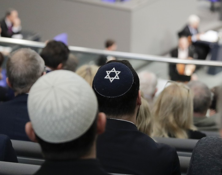 In this Thursday, Jan. 31, 2019, file photo, two men wearing skullcaps as they listen to the speech of Israeli Historian Saul Friedlaender, during a remembrance event of the parliament Bundestag to commemorate the victims of the Holocaust at the Reichstag building in Berlin. AP