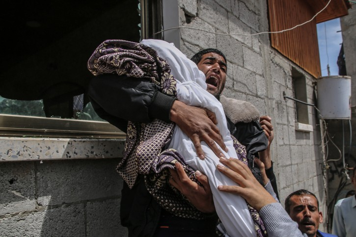 A Palestinian relative of fourteen-month baby girl Seba Abu-Arrar carries her body during her funeral with her relative woman in Al-Zaitun neighborhood in the east of Gaza City on, 05 May 2019.  EPA