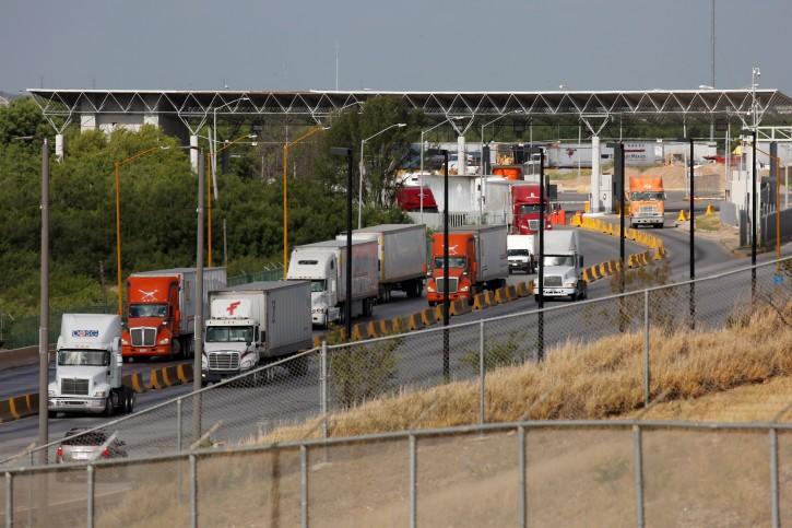 Trucks cross the borderline into the U.S. before border customs control at the World Trade Bridge, as seen from Laredo, Texas U.S., June 3, 2019. REUTERS/Carlos Jasso
