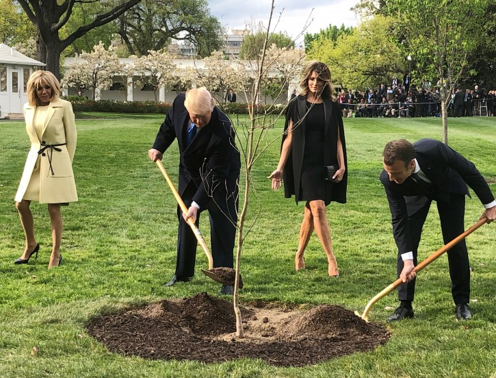 FILE - U.S. President Donald Trump and French President Emmanuel Macron shovel dirt onto a freshly planted oak tree as Brigitte Macron and first lady Melania Trump watch during a tree planting ceremony on the South Lawn of the White House in Washington, U.S., April 23, 2018.   REUTERS/Steve Holland