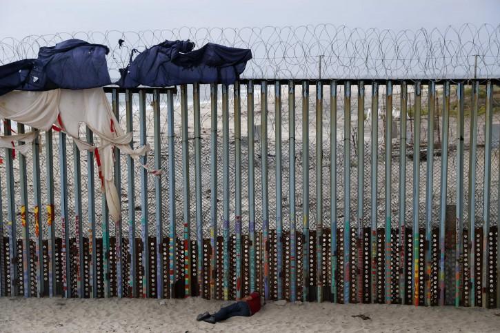 A man sleeps next to the U.S. border wall topped with razor wire in Tijuana, Mexico, Sunday, June 9, 2019. (AP Photo/Eduardo Verdugo)