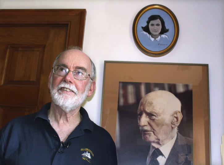 In this June 7, 2019 photo, Ryan Cooper stands next to a photo of Otto Frank, the father of the famed Holocaust victim and diarist Anne Frank, at his home in Yarmouth, Mass.  (AP Photo/Philip Marcelo)