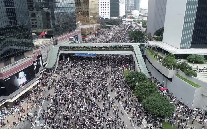 In this image made from aerial video, protesters gather in the streets outside the Legislative Council in Hong Kong, Wednesday, June 12, 2019. Thousands of protesters have blocked access to Hong Kong's legislature and government headquarters in a bid to block debate on a highly controversial extradition bill that would allow accused people to be sent to China for trial. (Apple Daily via AP)