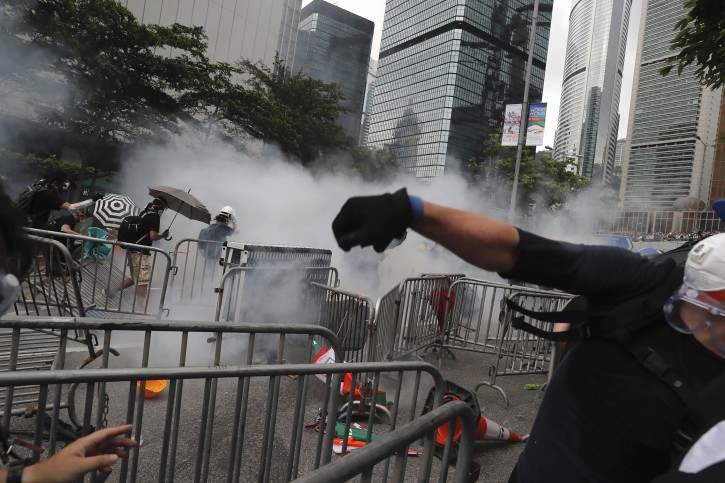 Protestors react to tear gas during protest near the Legislative Council in Hong Kong, Wednesday, June 12, 2019. Hundreds of protesters surrounded government headquarters in Hong Kong Wednesday as the administration prepared to open debate on a highly controversial extradition law that would allow accused people to be sent to China for trial.(AP Photo/Kin Cheung)