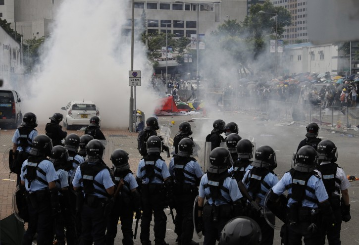 Riot police fire tear gas to protesters outside the Legislative Council in Hong Kong, Wednesday, June 12, 2019. Hundreds of protesters have blocked access to Hong Kong's legislature and government headquarters in a bid to block debate on a highly controversial extradition bill that would allow accused people to be sent to China for trial. (AP Photo/Vincent Yu)