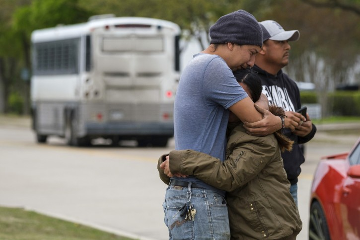 FILE - In this April 3, 2019, file photo, a couple who did not want to give their names embrace outside CVE Group as a bus from LaSalle Corrections Transport departs the facility in Allen, Texas. AP