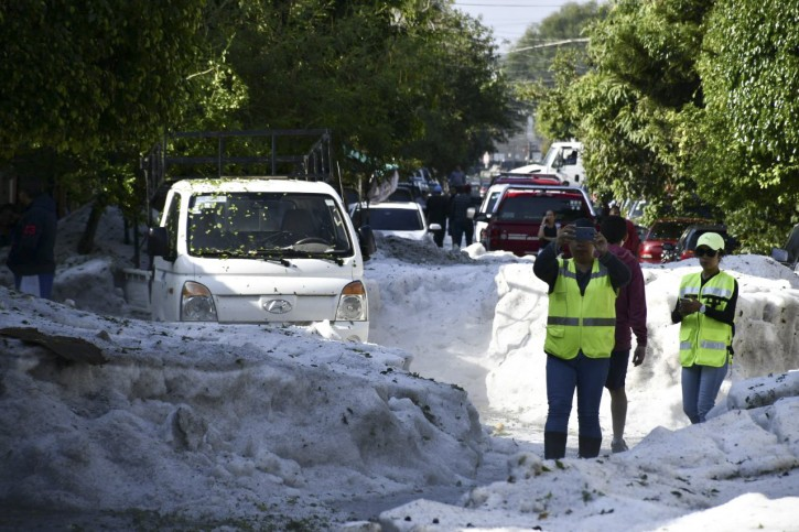 In this photo released by Jalisco State Civil Defense Agency, people take pictures of the streets filled with hail in Guadalajara, Mexico, Sunday, June 30, 2019. Officials in Mexico's second largest city say a storm that dumped more than a meter of hail on parts of the metropolitan area damaged hundreds of homes. (Jalisco State Civil Defense Agency via AP)