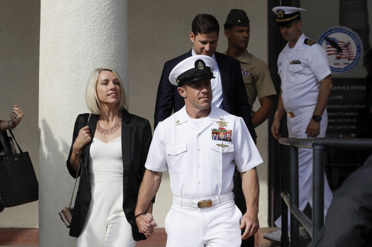 Navy Special Operations Chief Edward Gallagher, center, walks with his wife, Andrea Gallagher, as they leave a military court on Naval Base San Diego, Tuesday, July 2, 2019, in San Diego. (AP Photo/Gregory Bull)