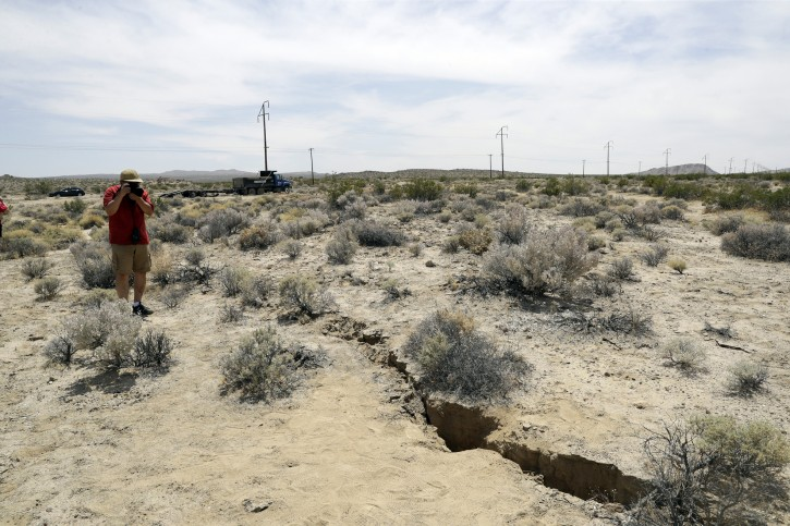 A visitor takes a photo of a crack on the ground following recent earthquakes Sunday, July 7, 2019, outside of Ridgecrest, Calif. (AP Photo/Marcio Jose Sanchez)