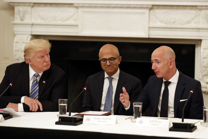 FILE - In this June 19, 2017, file photo President Donald Trump, left, and Satya Nadella, Chief Executive Officer of Microsoft, center, listen as Jeff Bezos, Chief Executive Officer of Amazon, speaks during an American Technology Council roundtable in the State Dinning Room of the White House in Washington.  (AP Photo/Alex Brandon, File)
