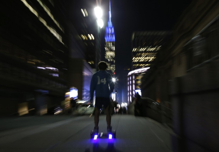 FILE - In this Wednesday Oct. 21, 2015 file photo, a young man rides a hoverboard along a Manhattan street toward the Empire State Building, in New York.  (AP Photo/Kathy Willens, File)