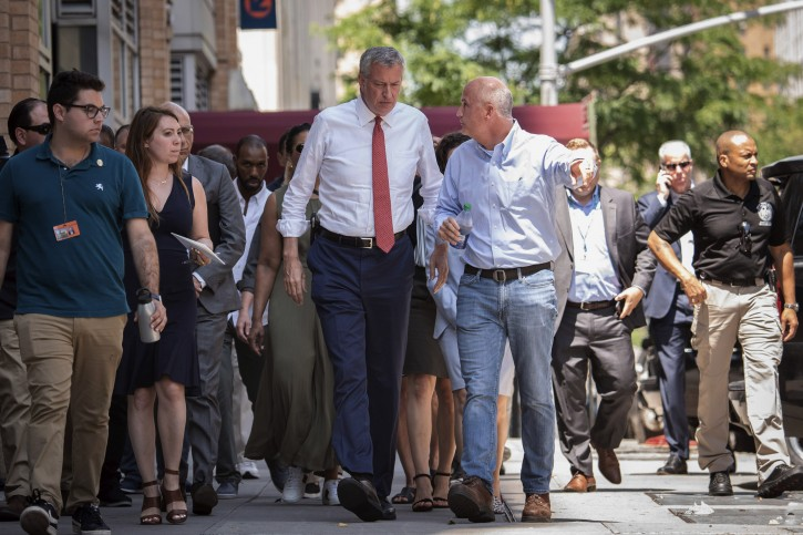 New York Mayor Bill de Blasio, left center, listens to ConEd President Tim Cawley, right center, Sunday, July 14, 2019, as the mayor visits the site of Saturday night's power outage, on New York's Upper West Side. AP