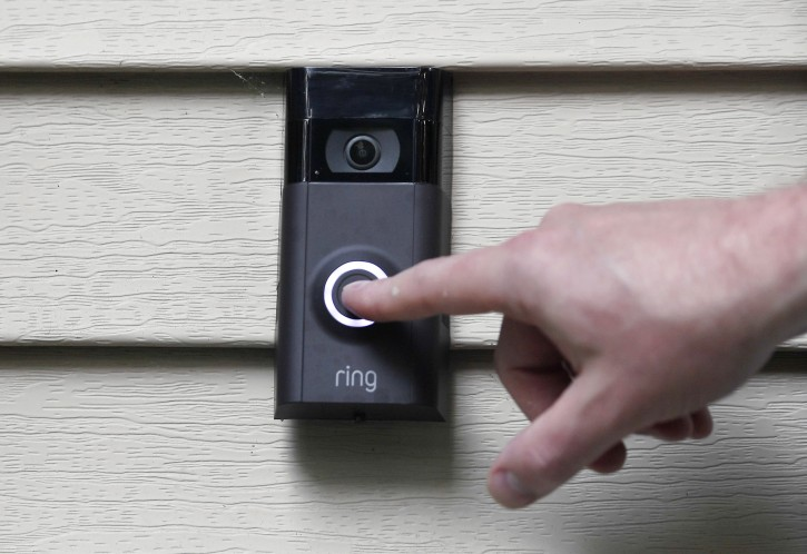 In this Tuesday, July 16, 2019, Ernie Field pushes the doorbell on his Ring doorbell camera at his home in Wolcott, Conn. (AP Photo/Jessica Hill)