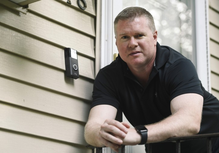 In this Tuesday, July 16, 2019, Ernie Field poses for a photograph next to a Ring doorbell camera at his home in Wolcott, Conn. (AP Photo/Jessica Hill)