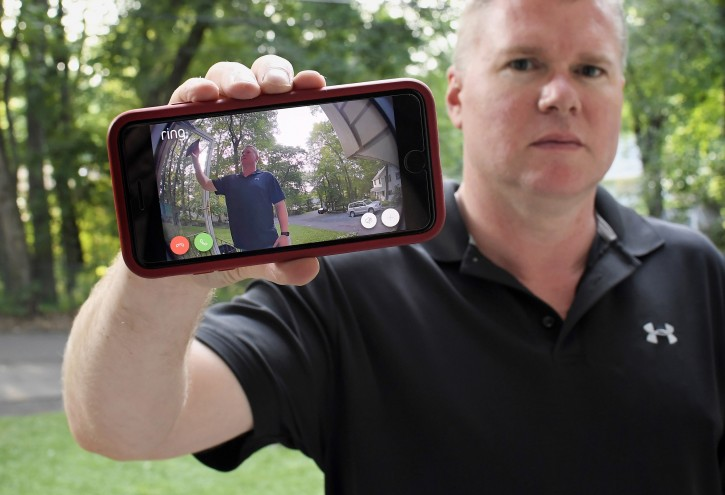 In this Tuesday, July 16, 2019, Ernie Field holds up a live video of himself taken by a Ring doorbell camera at the front door at his home in Wolcott, Conn. (AP Photo/Jessica Hill) AP