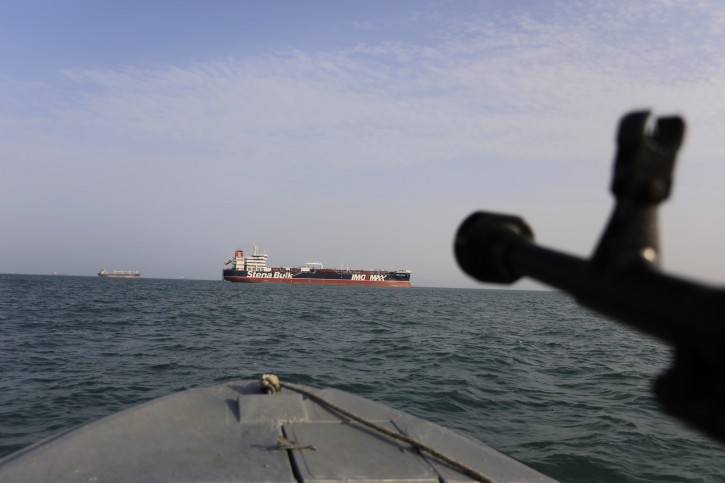 In this Sunday, July 21, 2019 photo, a speedboat of the Iran's Revolutionary Guard sails around a British-flagged oil tanker Stena Impero, at rear, which was seized in the Strait of Hormuz on Friday by the Guard, in the Iranian port of Bandar Abbas.  (Morteza Akhoondi/Tasnim News Agency via AP)