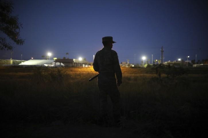 Military police wearing the insignia of the National Guard patrol near the border bridge that crosses the Rio Grande river, in Matamoros, Mexico, Friday, Aug. 2, 2019. (AP Photo/Emilio Espejel)