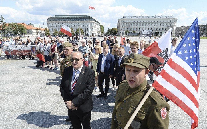 Polish officials and war veterans pay tribute to a World War II-era underground force that collaborated with Nazi German forces toward the end of the war in their battle against the Communists, who were imposing control on the nation, in Warsaw, Poland, Sunday, Aug. 11, 2019. AP