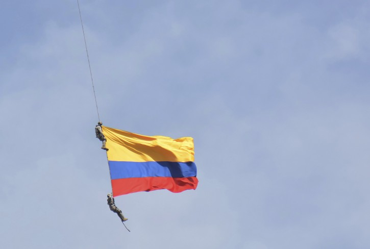 Two members of Colombia´s air force hang from a cable under a helicopter flying a Colombian flag, before plunging to their deaths when the cable snapped during the mid-air stunt at the Medellin Flower Fair in Medellin, Colombia, Sunday, Aug. 11, 2019. (AP Photo/Luis Benavides)