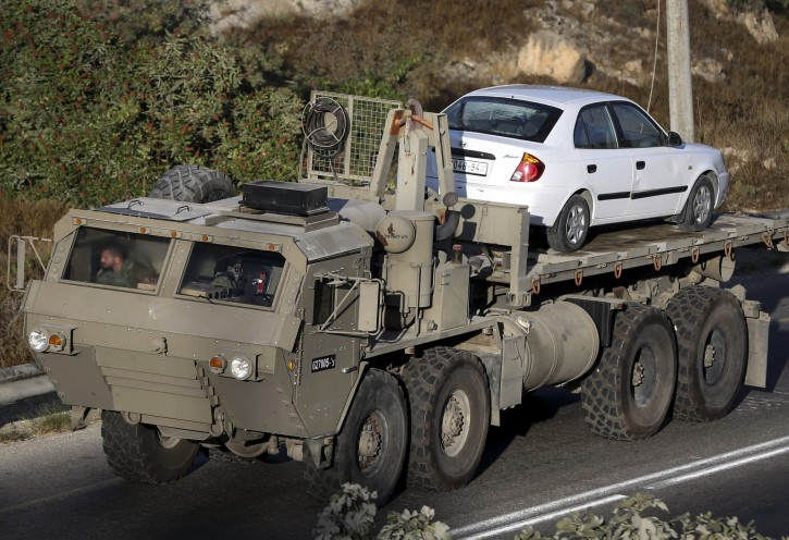 An Israeli army vehicle carries a Palestinian car in the West Bank village of Beit Kahil on August 10, 2019. Four Palestinians were arrested after Israeli focres raided the village in search of the killers of an Israeli soldier who was found stabbed to death two days before in Gush Etzion. 18-year-old soldier, Dvir Yehuda Sorek was found dead with stabbing wounds near the Jewish settlement of Migdal Oz. Photo by Wisam Hashlamoun/Flash90